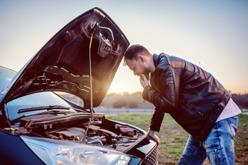 Young serious handsome caucasian bearded blond man in leather jacket looking engine of his car under the hood. Something went wrong. Fotomurales