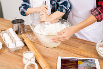 Hands of young woman holding bowl while her little son whisking eggs with flour