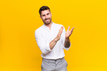 young handosme man feeling happy and successful, smiling and clapping hands, saying congratulations with an applause against flat color wall