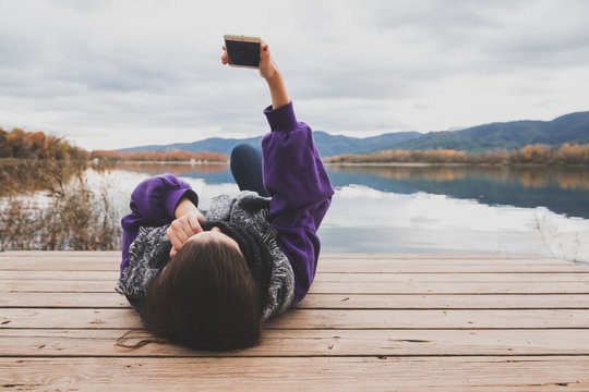 young girl lying making a selfie in a lake