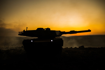 War Concept. Armored vehicle silhouette fighting scene on war fog sky background. American tank at sunset. Fototapete