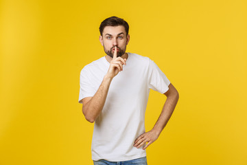 young man making silence gesture, shhhhh. Isolated over yellow background.