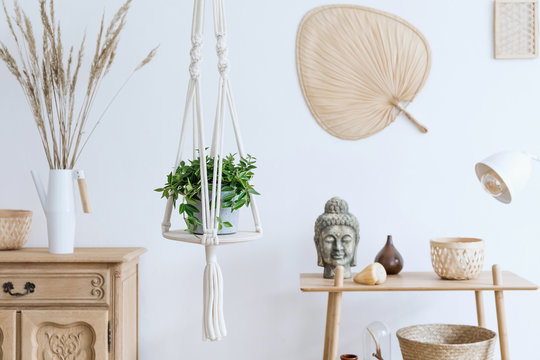 Minimalistic boho interior with design and handmade macrame shelf planter hanger for indoor plants, wooden furnitures, elegant accessories ,rattan basket and leaf. Cozy home decor of living room.
