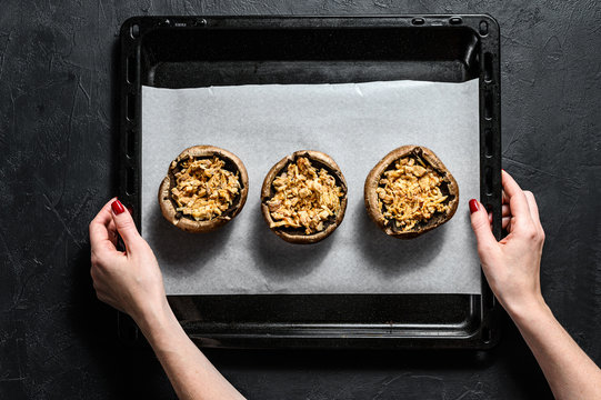 The chef prepares stuffed Portobello mushrooms. Gray background. Top view. Space for text