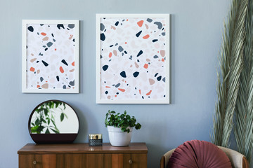 The stylish scandinavian interior of living room at design apartment with mock up poster frames...