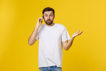 Portrait of a serious man talking on the phone isolated on a yellow background. Looking at camera