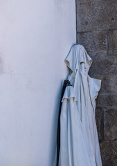 Folded street or table umbrella looks like a ghostly cloth costume with hood and eyes