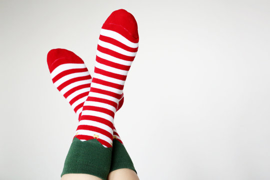 Female feet in Christmas socks on white background. Concept of New Year celebration, elf costume