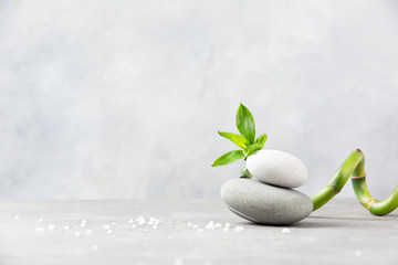Spa concept. Bamboo, sea salt and sea stones on grey background. Copy space.