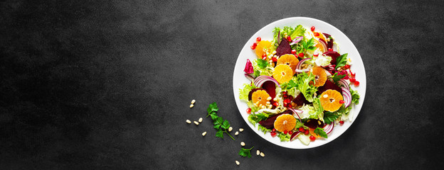 Christmas salad with boiled beet, red onion, tangerines, pomegranate, parsley, pine nuts and lettuce leaves