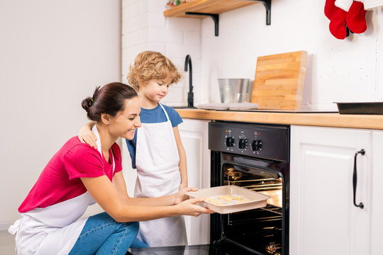 Little boy standing by his happy mother putting tray with biscuits into oven
