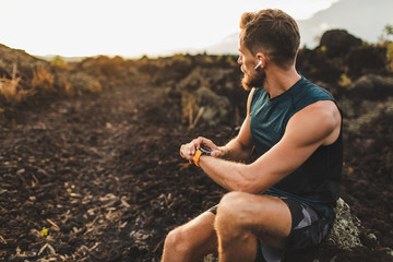 Athletic runner start training on fitness tracker or smart watch and looking forward on horizon. Trail running and active lifestyle concept.
