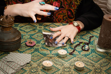 Gypsy psychic looking for a man in a photo using a pendulum. Love spell on photos