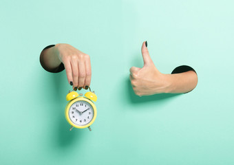 Female hand hold alarm clock and show tumb sign through a hole on neon mint background. Just in time concept.