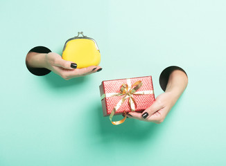 Female hands hold red gift and wallet through a hole on neon mint background. Isolated sale concept.