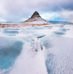 Famous mountain with waterfalls in Iceland,  kirkjufell, winter in Iceland, ice and snow, reflections, yellow grass, nature, icelandic famous landscape