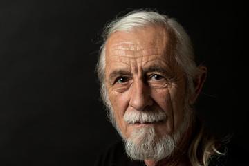 Closeup low key studio portrait of beautiful gray hair old man looking at the camera. Horizontally. Fotomurales