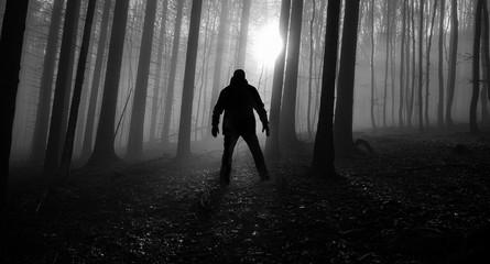 one alone man in a foggy dark forest