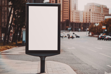 A blank vertical street poster template on a sidewalk near a highway; an outdoor billboard placeholder mockup near a road with cars; mock-up of an empty advertising banner near in urban settings