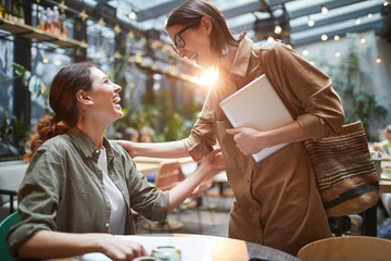 Side view portrait of two young women greeting each other joyfully during meeting in cafe on outdoor terrace decorated with lights