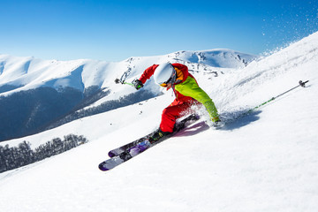 Wall Mural - A man is skiing down the hill on the steep slope in Carpathians. Ukraine. High mountain area.