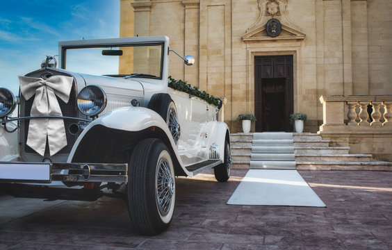 White classic car for a traditional wedding in front of a church