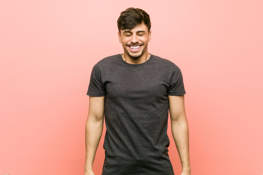 Young hispanic casual man laughs and closes eyes, feels relaxed and happy.