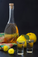 Quince brandy or quince vodka, hard liquor, strong drink in a bottle and glasses on dark background. Serebian traditional dring, rakija or rakia. Vertical image.