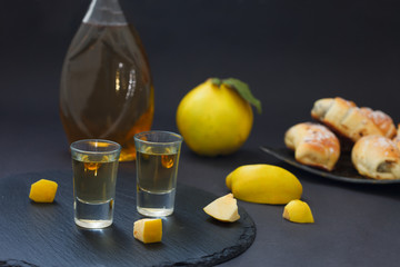 Quince brandy or quince vodka, hard liqueur, strong drink in a bottle and glasses on dark background. Serebian traditional dring, rakija or rakia.