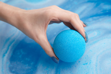Woman's hand putting bath bomb into water