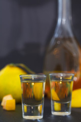 Quince alcoholic drink. Quince Brandy and fresh quinces on dark background, vertical image