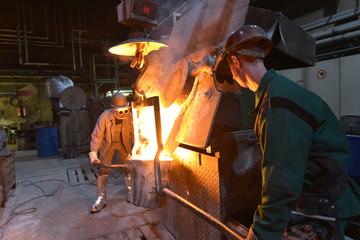 Arbeiter in einer Giesserei am Schmelzofen // Worker in a foundry at the melting furnace