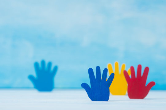 Colorfull puzzles hands on blue background. World Autism Awareness Day Concept