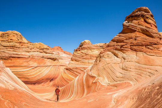 Young man hiking through Coyote Buttes and the famous Wave feature of Arizona.