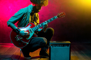 Portrait of hipster man with curly hair with red guitar in neon lights. Rock musician is playing electrical guitar.