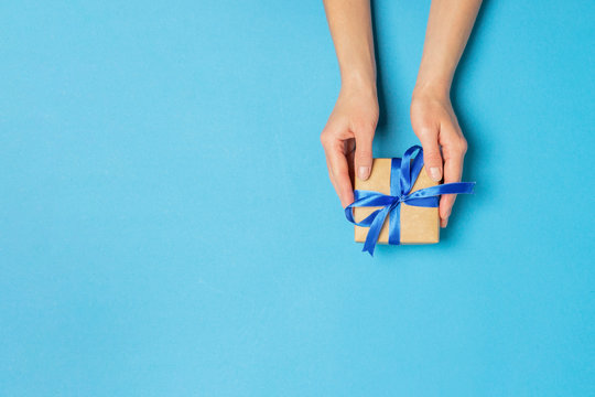 Female hand holds, takes, get a gift on a blue background. Concept gift, wedding, valnetina day. Flat lay, top view