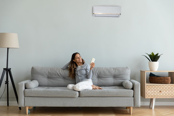 Fototapeta Woman holding remote control manages degrees enjoy air-conditioned flat obraz
