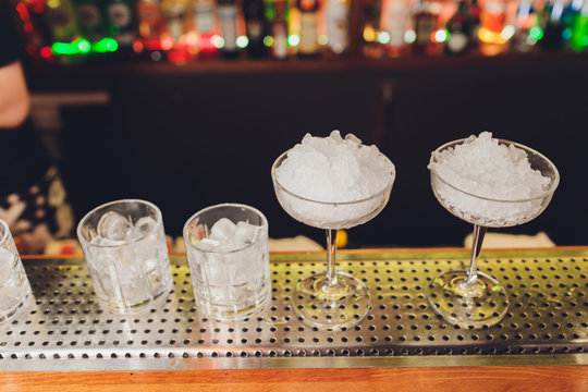 A bartender makes a cocktail over the marble bar counter.