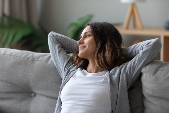 Woman put hands behind head leaned on couch resting indoors