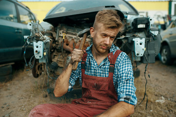 Male repairman sitting on the ground, car junkyard