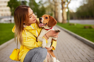 Woman hugging adorable dog while walking in street Wall mural