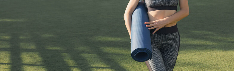 In de dag Ontspanning A young slim athletic girl in sportswear with snakeskin prints performs a set of exercises. Twists the yoga mat on the background of lawn grass. Panoramic image, toned.