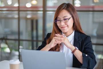 Closeup image of businesswoman looking at laptop while working in office
