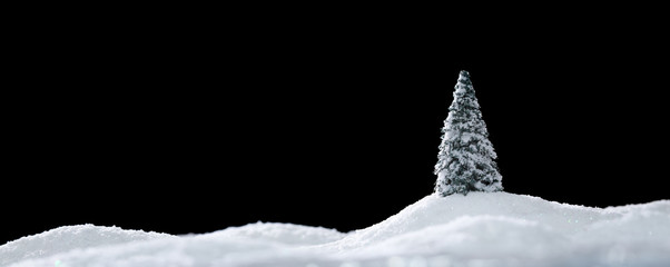 Wintery landscape with single tree on glistening white snow drifts isolated on black
