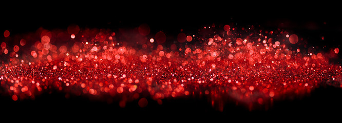 Bokeh of sparkling red lights and glitter on black