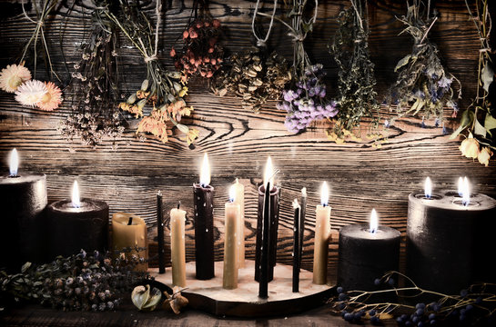 Black candles, herbs and flowers against wooden wall on witch table.