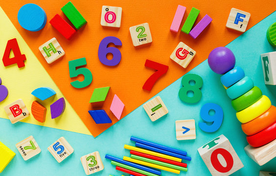 Wooden kids toys on colourful paper. Educational toys blocks, pyramid, pencils, numbers, train. Toys for kindergarten, preschool or daycare. Copy space for text. Top view