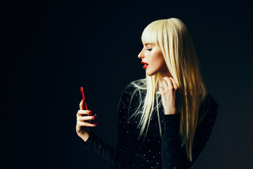 Profile portrait of a beautiful blonde woman  holding a redsmartphone ,isolated on black studio background