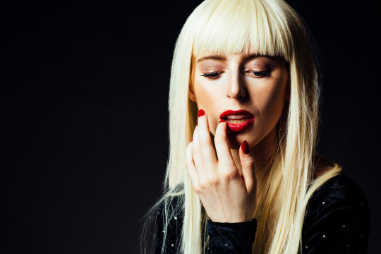 Portrait of a beautiful platinum blonde female model with red fingernails and red lips