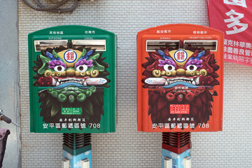 Taiwan - May 4, 2015: Green and red post boxes decorated with Chinese lion on a street in Tainan.